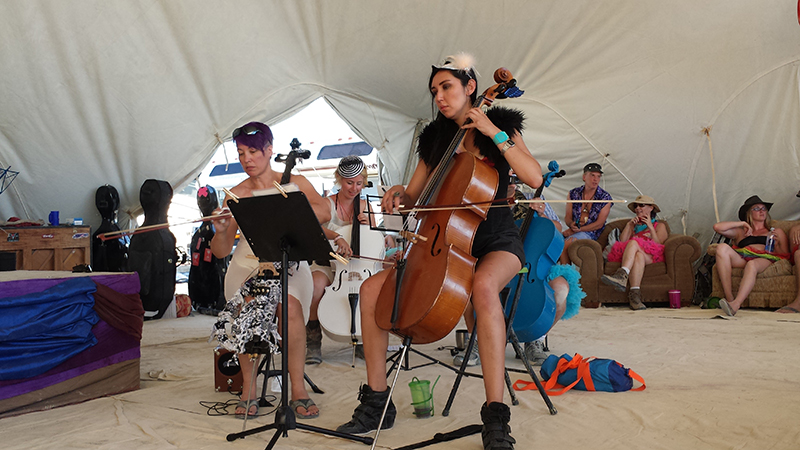 Cellists with the PlayaPops Symphony warm up before their debut performance at Burning Man this year (2014).