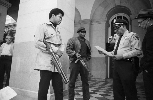 Two members of the Black Panther Party are met on the steps of the California State Capitol in Sacramento, May 2, 1967, by Police Lt. Ernest Holloway, who informs them they will be allowed to keep their weapons as long as they cause no trouble and do not disturb the peace. Earlier several members had invaded the Assembly chambers and had their guns taken away; Bettmann/CORBIS