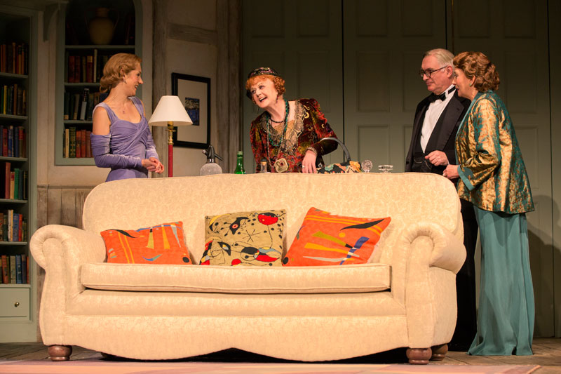 Ruth (Charlotte Parry) and guests  the Bradmans (Simon Jones and Sandra Shipley) greet medium Madame Arcati in Blithe Spirit.