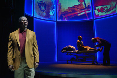 Former 49er Dwight Hicks talks football injuries while Marilee Talkington examines Eddie Ray Jackson in X's and O's (A Football Love Story) at Berkeley Repertory Theatre.