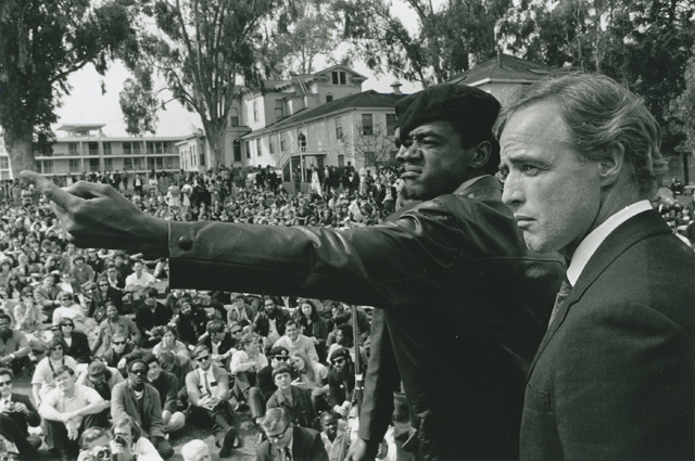 Bobby Seale and Marlon Brando at the at the memorial for Bobby Hutton, April 12, 1968, at Merritt Park in Oakland. (Photo: Jeffrey Blankfort)