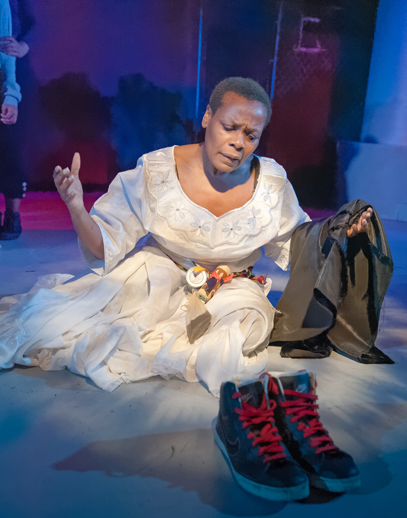 Spirit (Awele Makeba) recognizes the symbolization of shoes as the dead in African-American Shakespeare Company's Xtigone. (Photo: Lance Huntley)