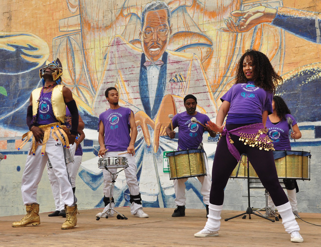 A dance troupe rehearses while Duke Ellington, in mural form, looks on at the African American Art and Culture Complex.