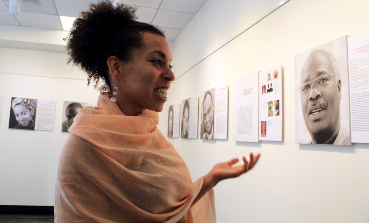 Curator of the events at the Goethe Institut, Victoria Toney-Robinson, explains the Homestory Deutschland exhibit. (Photo: Lakshmi Sarah/KQED)