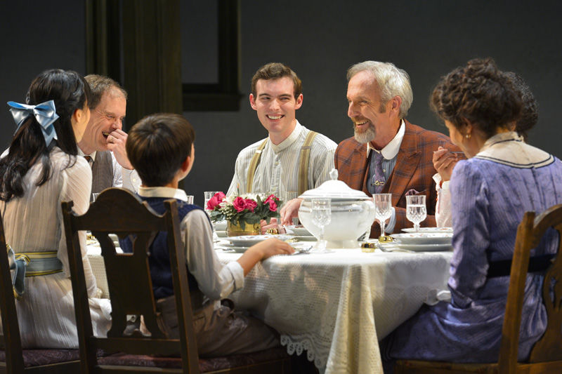 Sid Davis (Dan Hiatt, pictured in orange suit) indulges the Miller family with food gags at the dinner table in Eugene O'Neill's Ah, Wilderness!, performing at A.C.T.'s Geary Theater through Sunday, November 8.