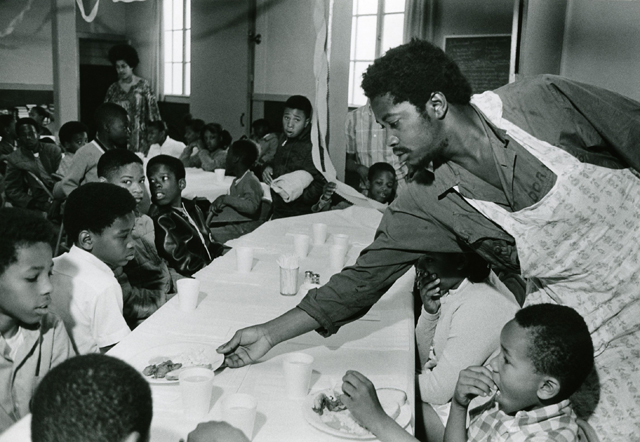 Charles Bursey hands plate of food to a child seated at Free Breakfast Program.