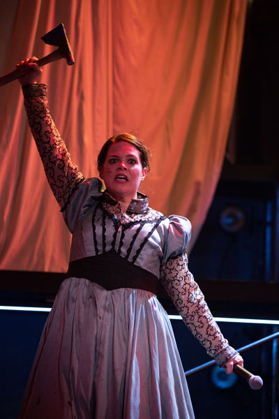 Lizzie (Elizabeth Curtis) gets ready to axe the parents in a musical at Ray of Light Theatre