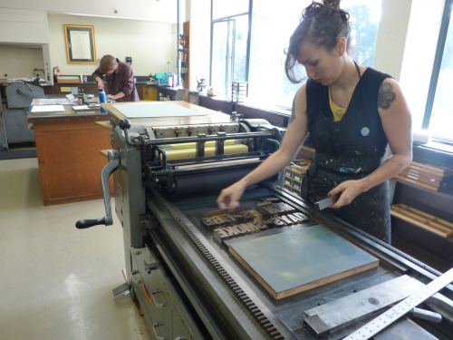 Beck Levy and Isabel Duffy (in the background) work on the presses at Mills College. (Photo: Jess Heaney)