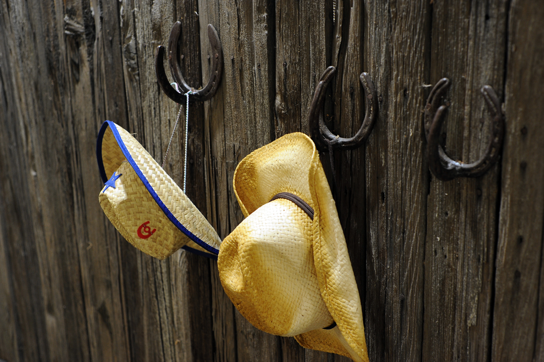 "Cowboy hats hanging on low hooks for children to wear at NUMU's ""It Takes a Village"" exhibit. Photo by Adrienne Blaine."