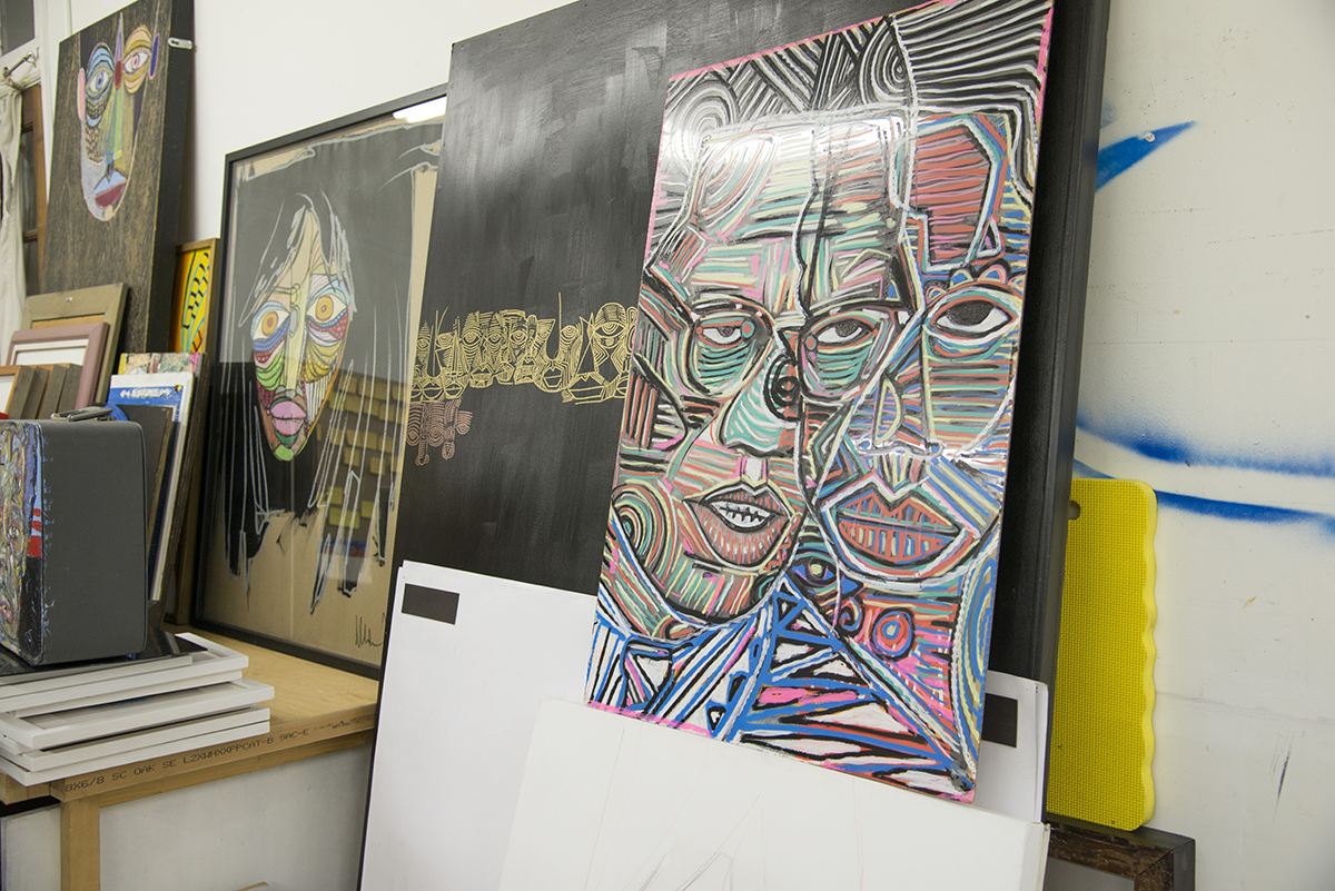 Paintings line the walls of Tesfai's studio.