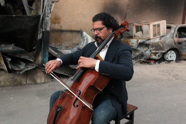 Karim Wasfi, former director for the Iraqi National Symphony Orchestra, plays on his cello next to debris in Baghdad's Sunni Adhamiya district on May 15, 2015, in a symbolic act of protest against violence.