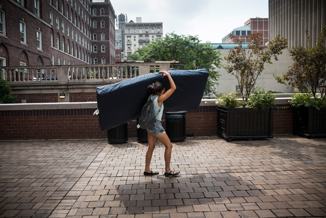 Emma Sulkowicz carries a mattress in protest of Columbia University's lack of action.