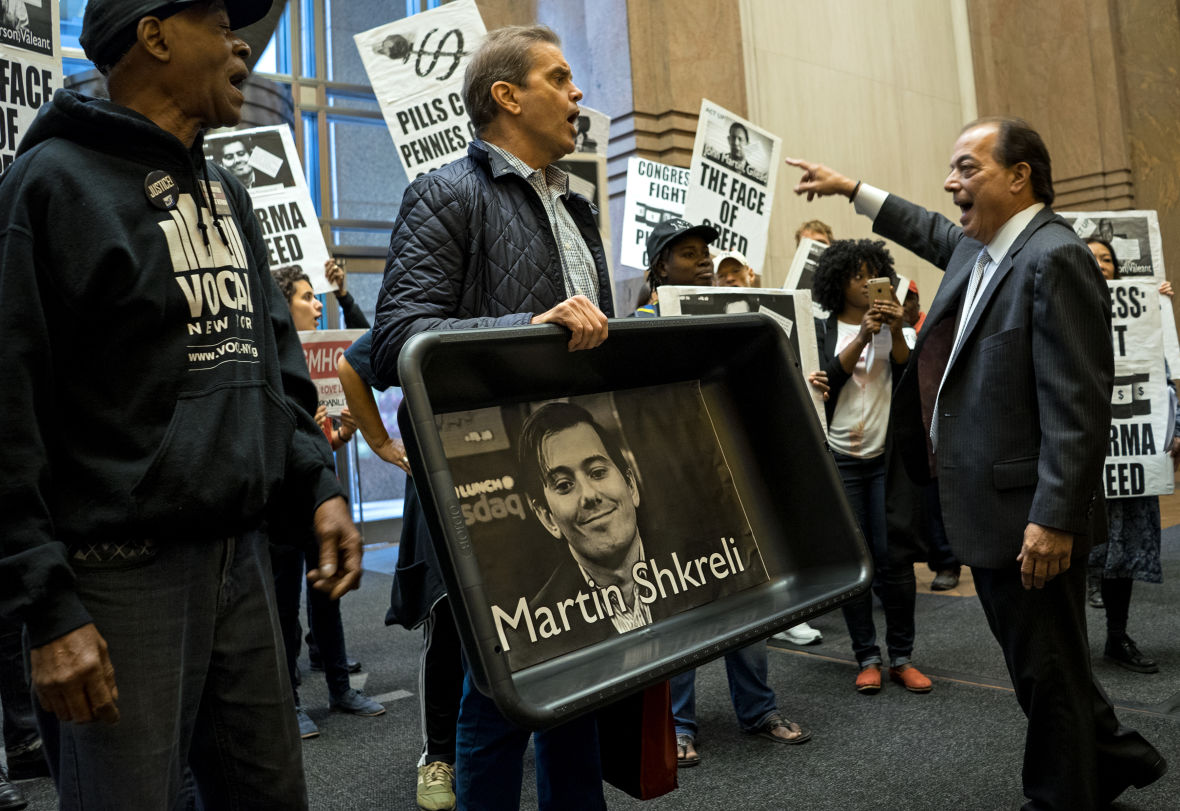 """AIDS activists and others carry an image of Turing Pharmaceuticals CEO Martin Shkreli and signs decrying """"Pharma greed"""" during a protest Oct. 1. Shkreli's company bought an antiparasitic drug and increased the price 5,000 percent."""