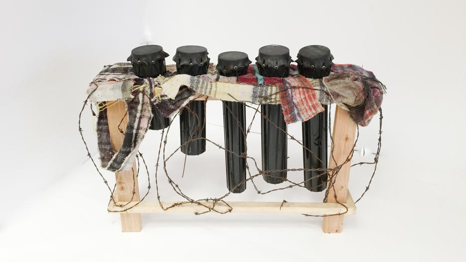 'Llantambores,' drums caped with skin made from inner tubes used to cross the Rio Grande in Texas and wedged into a structure fashioned out of carpet booties used by immigrants to hide their footsteps; barbed wire that once served as the fence between the two nations surrounds.