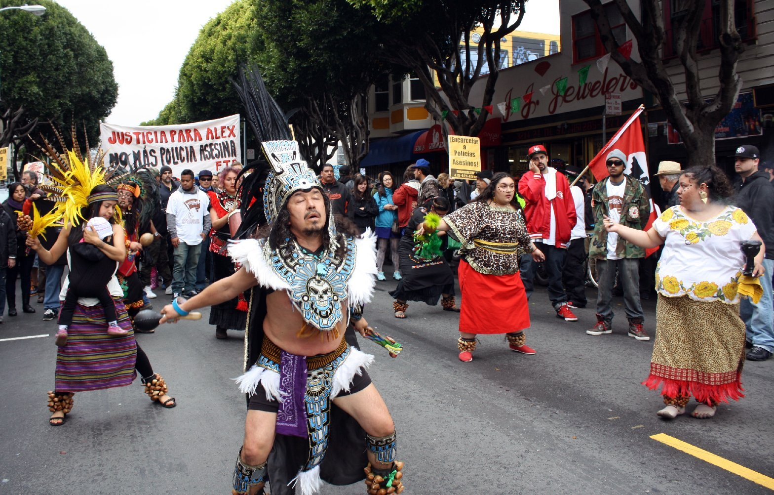 Aztec dancers march for Alejandro Nieto in March 2014.