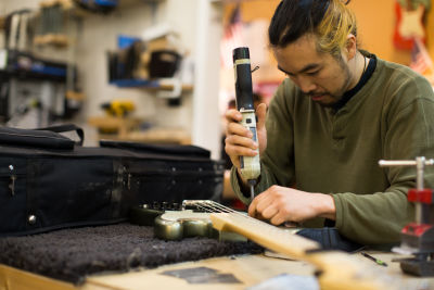 Staff member Tomm Nguyen hard at work on a guitar.