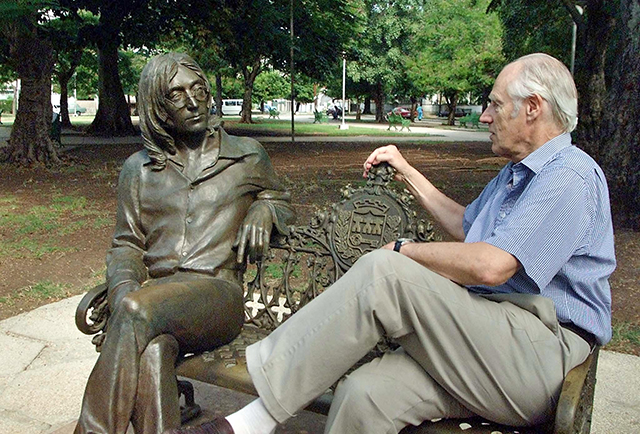 Sir George Martin (R), known world-wide as the fifth Beatle from his collaborations with the famous musical group, shares a seat with a statue of John Lennon in a park of Havana, Cuba
