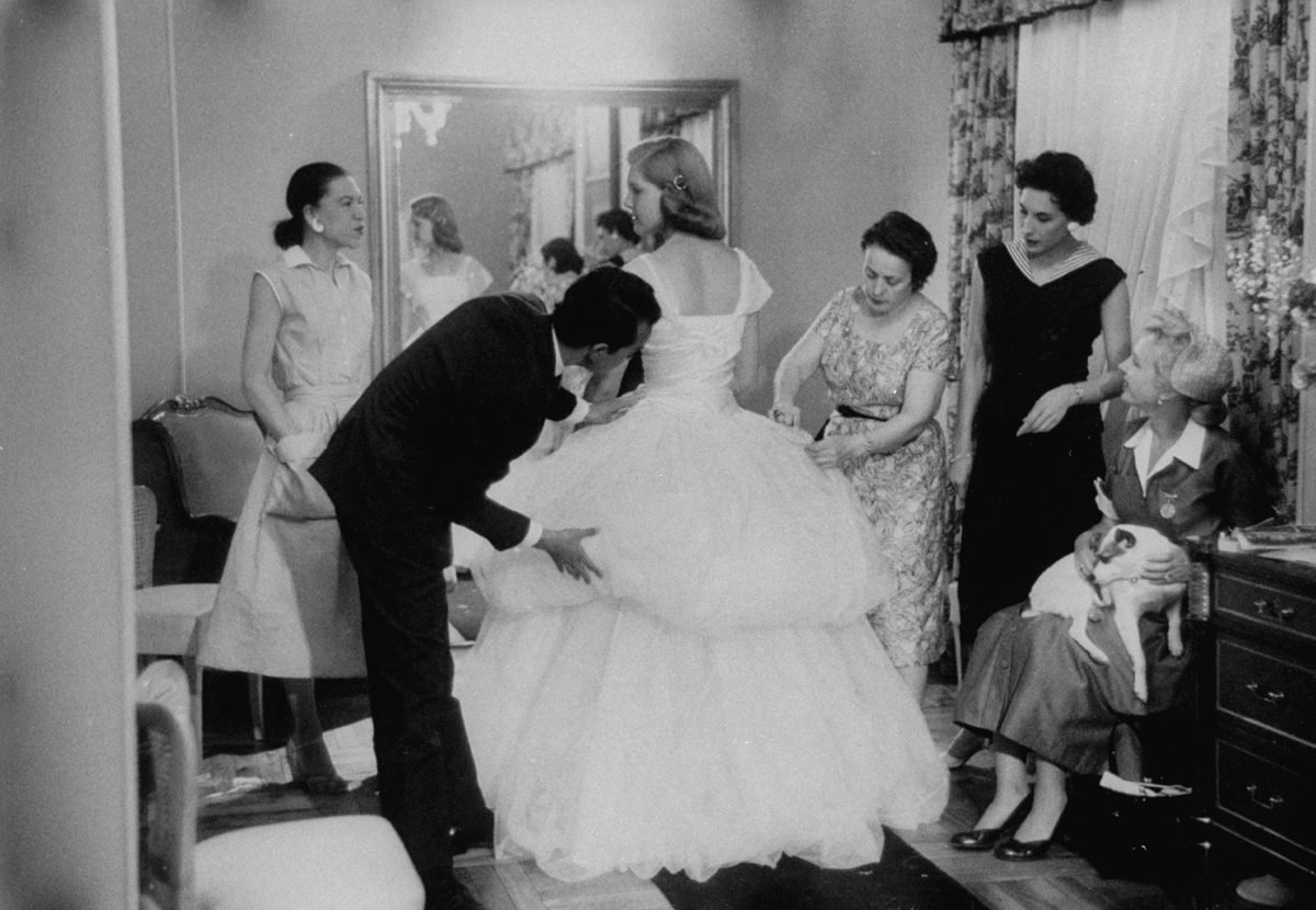 Baroness Aino Bodisco, looking on as Beatrice Lodge is being fitted by fashion designer Oscar de la Renta in her debutante dress.