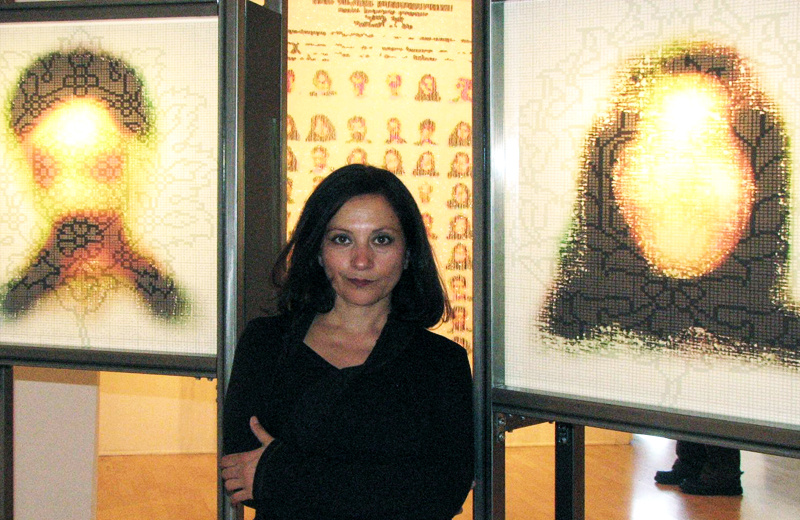 "Artist Taraneh Hemami poses in front of her ""Most Wanted"" installation, created out of beads, at the Intersection of the Arts in 2007."