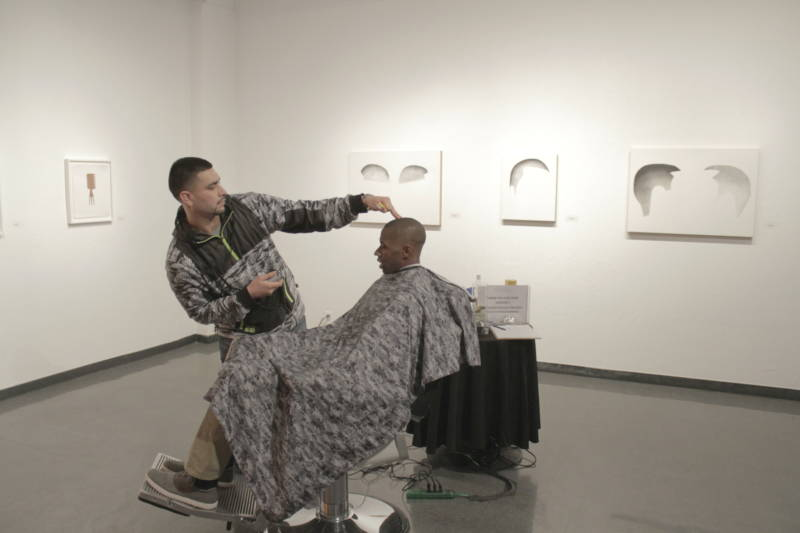 Jose the Barber, giving a MACLA visitor a close crop fade haircut at the Custom Lives opening in December 2015.