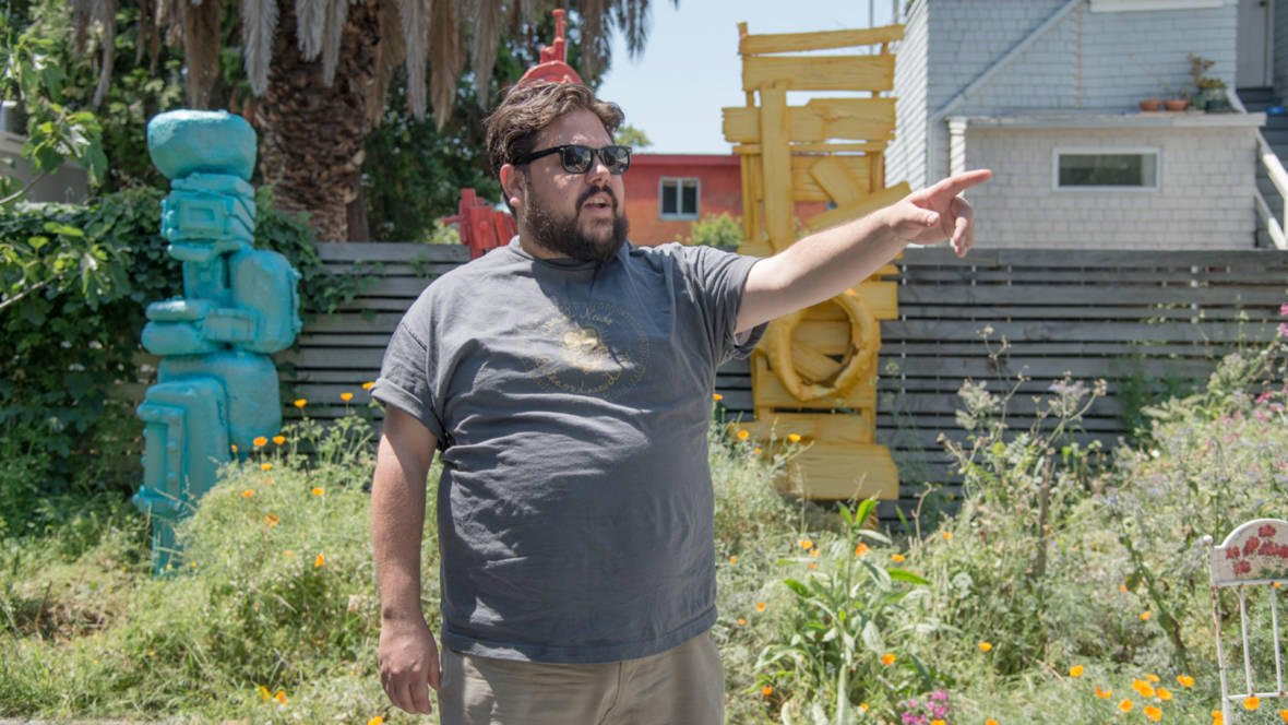 Joey Enos stands in the yard outside his Oakland home and studio, three sculptures in the background.  Photo: Graham Holoch/KQED