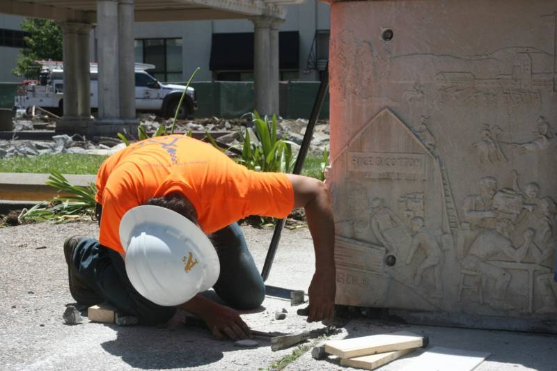 A worker helps remove a panel by artist Ruth Asawa from a fountain in Courthouse Square in Santa Rosa.