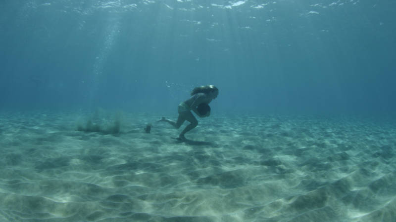 Paige Alms runs underwater with a heavy rock as part of her training to ride big waves.