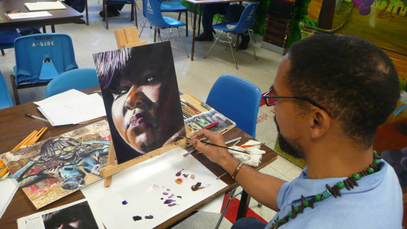 An inmate is putting final touches on an oil painting of actress Gabourey Sidibe.