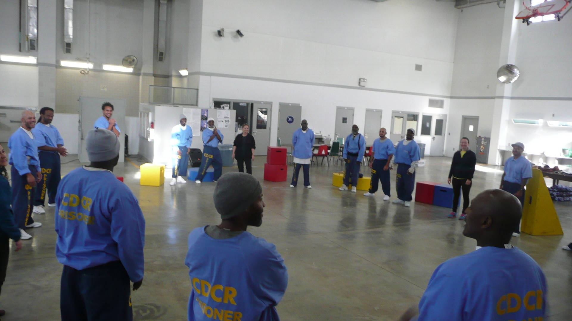 """Inmates in the improv class at Salinas Valley State Prison warm-up with a classic improvisation game called """"slap pass."""""""