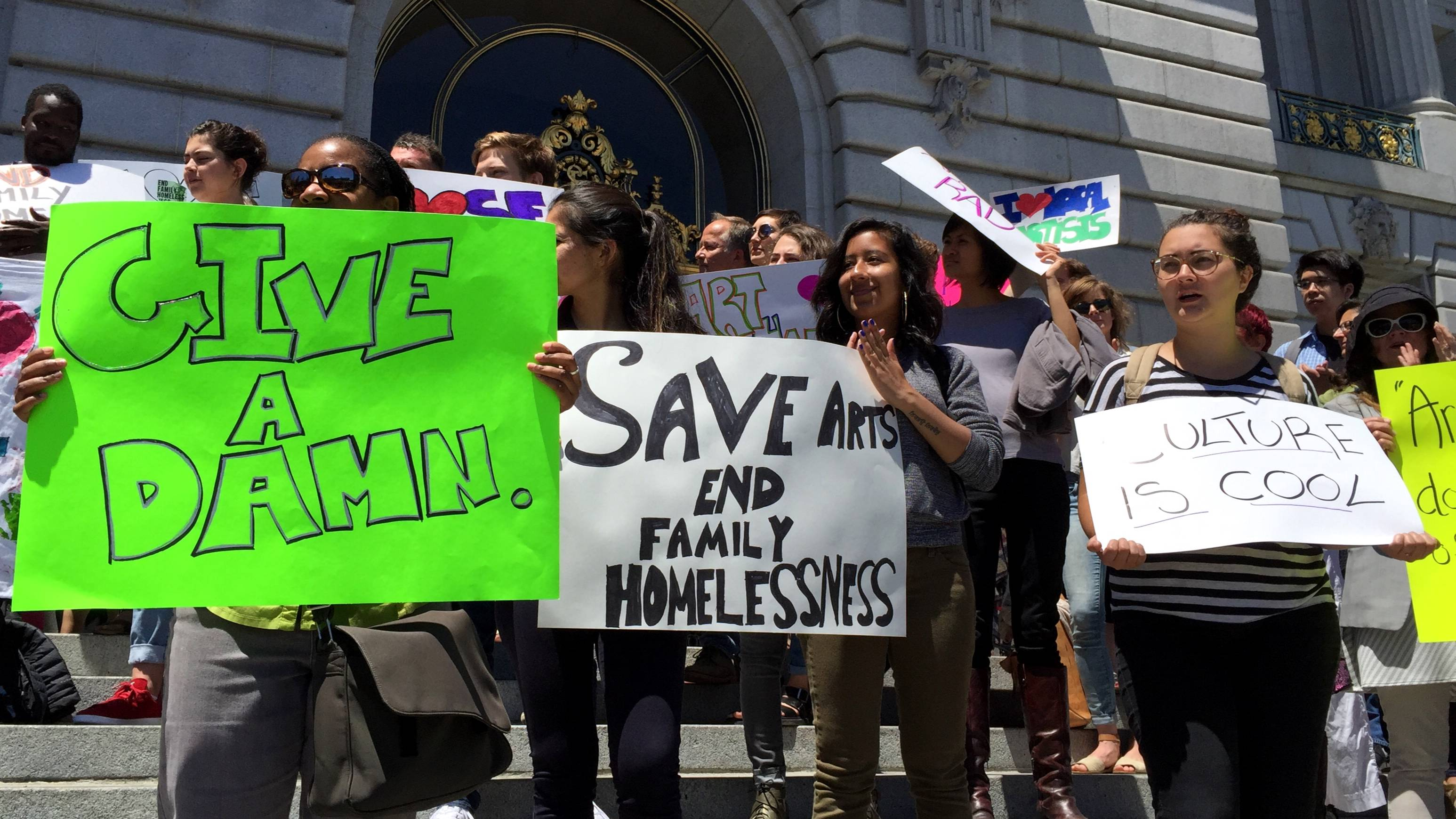 Supporters of a new ballot measure proposal to restore funding from the city's hotel tax to support arts organizations and homeless services participate in a rally at San Francisco City Hall