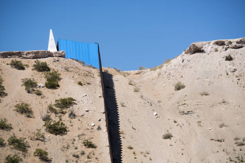 """U.S. Mexico Border fence is seen from Ciudad Juárez, Mexico after artist Ana Teresa Fernandez and Border/Arte volunteers painted the border fence in blue to give an illusion of """"Erasing the Border"""" on Saturday, April 9, 2016."""