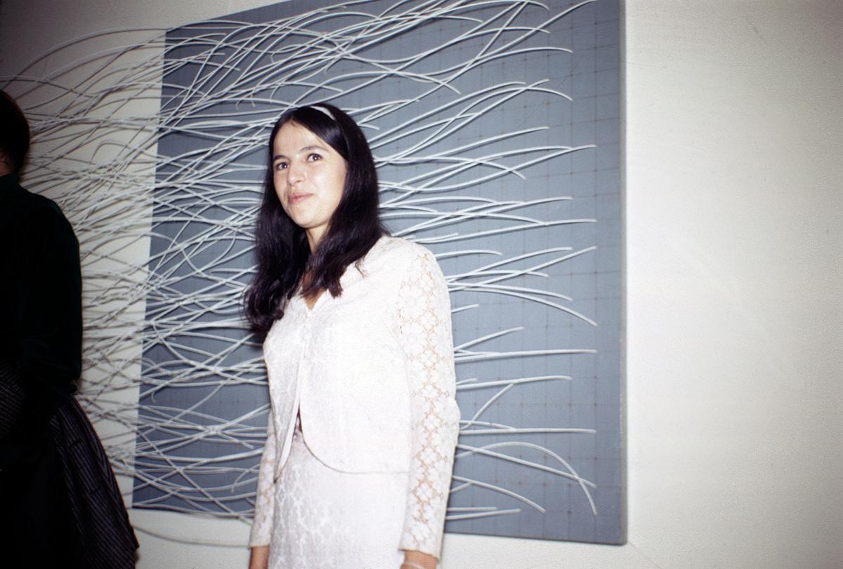 Eva Hesse in front of her work 'Metronomic Irregularity II,' in 'Eccentric Abstraction.'