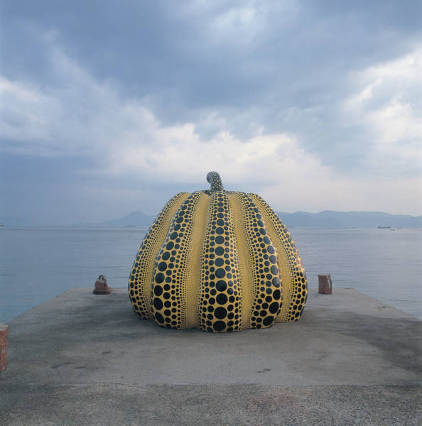 "Yayoi Kusama's work ""Pumpkin"" perches at the end of an old concrete pier."