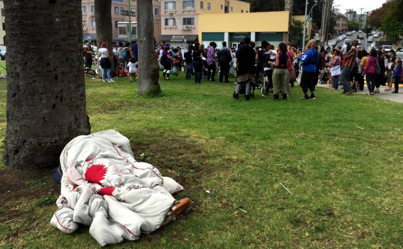 A homeless man sleeps a few feet away from Aaron Davis and his fellow drummers on Saturday near Lake Merritt