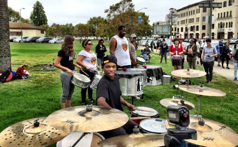 Aaron Davis at his drum kit at Eastshore Park with members of the drum corps Loco Bloco behind him