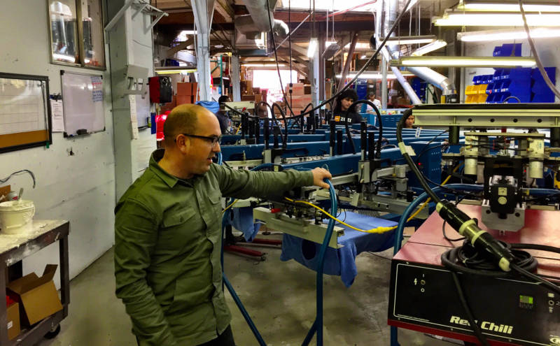 Kevin McKracken inspects his t-shirt screen printing line at Social Imprints, a branding company South of Market