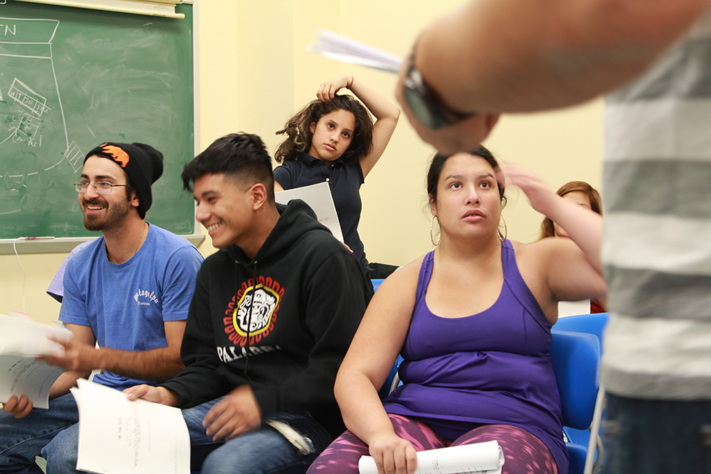 Cast members turn to Paul S. Flores for direction during rehearsal.