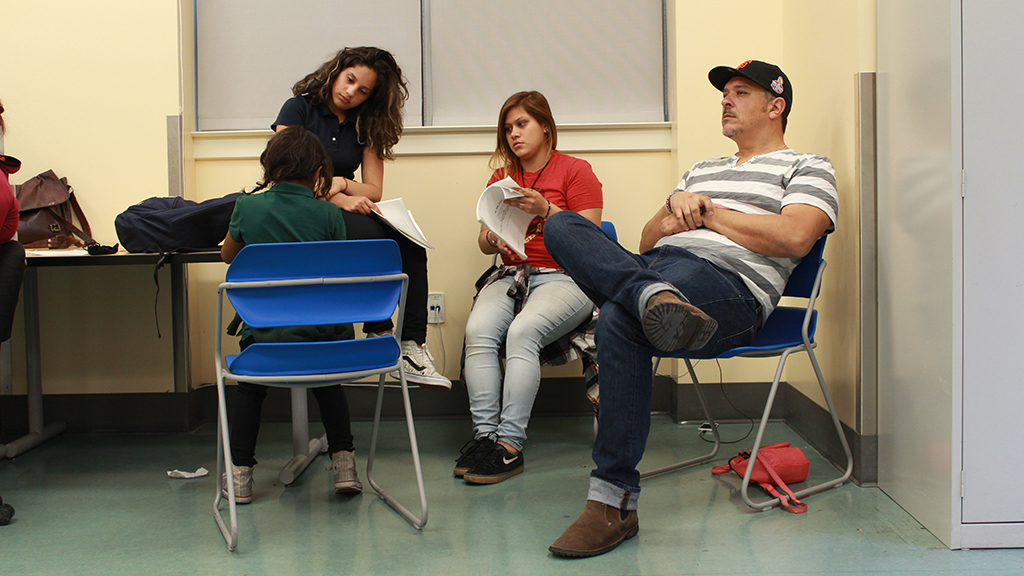 """Director and playwright Paul S. Flores watches intently as his cast rehearses scenes from """"On The Hill."""""""