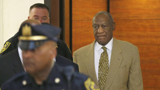 Bill Cosby, right, walks off the elevator to the second floor of the Montgomery County Courthouse.