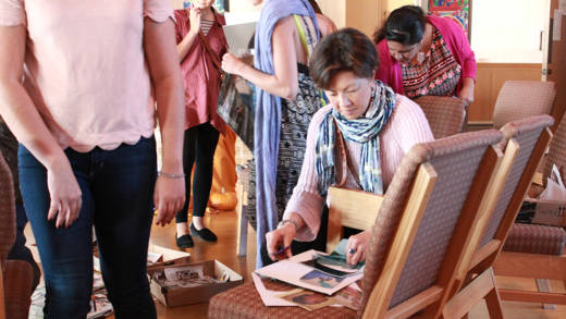 A Harvest Festival attendee cuts up magazine pages for her Guadalupe collage.