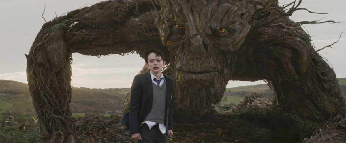 Conor (Lewis MacDougall) is shadowed by The Monster (performed and voiced by Liam Neeson) in J.A. Bayona's 'A Monster Calls.'
