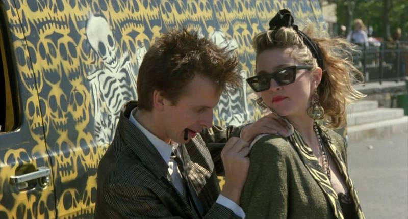 Robert Joy and Madonna in 'Desperately Seeking Susan,' standing near a van adorned with Michael Roman's skull stencil