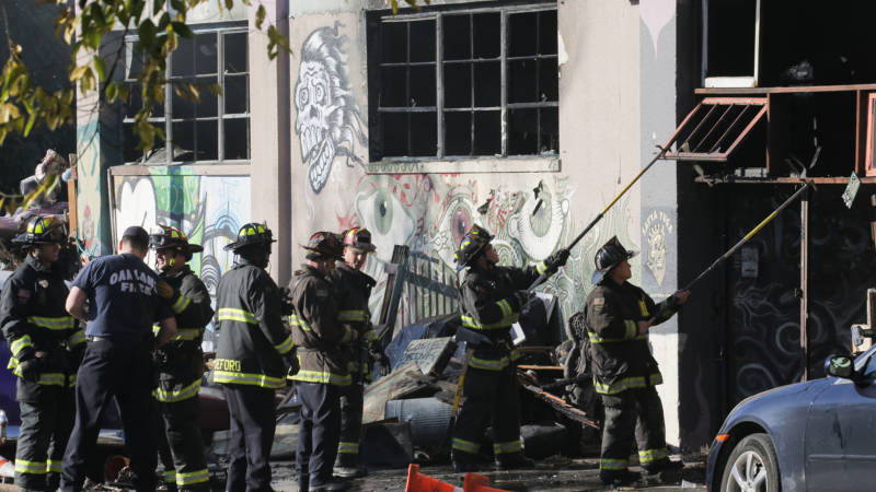 Firefighters work to clear the debris from a doorway following an overnight fire that claimed the lives of at least 36 people at a warehouse in Oakland's Fruitvale neighborhood on Dec 3, 2016.