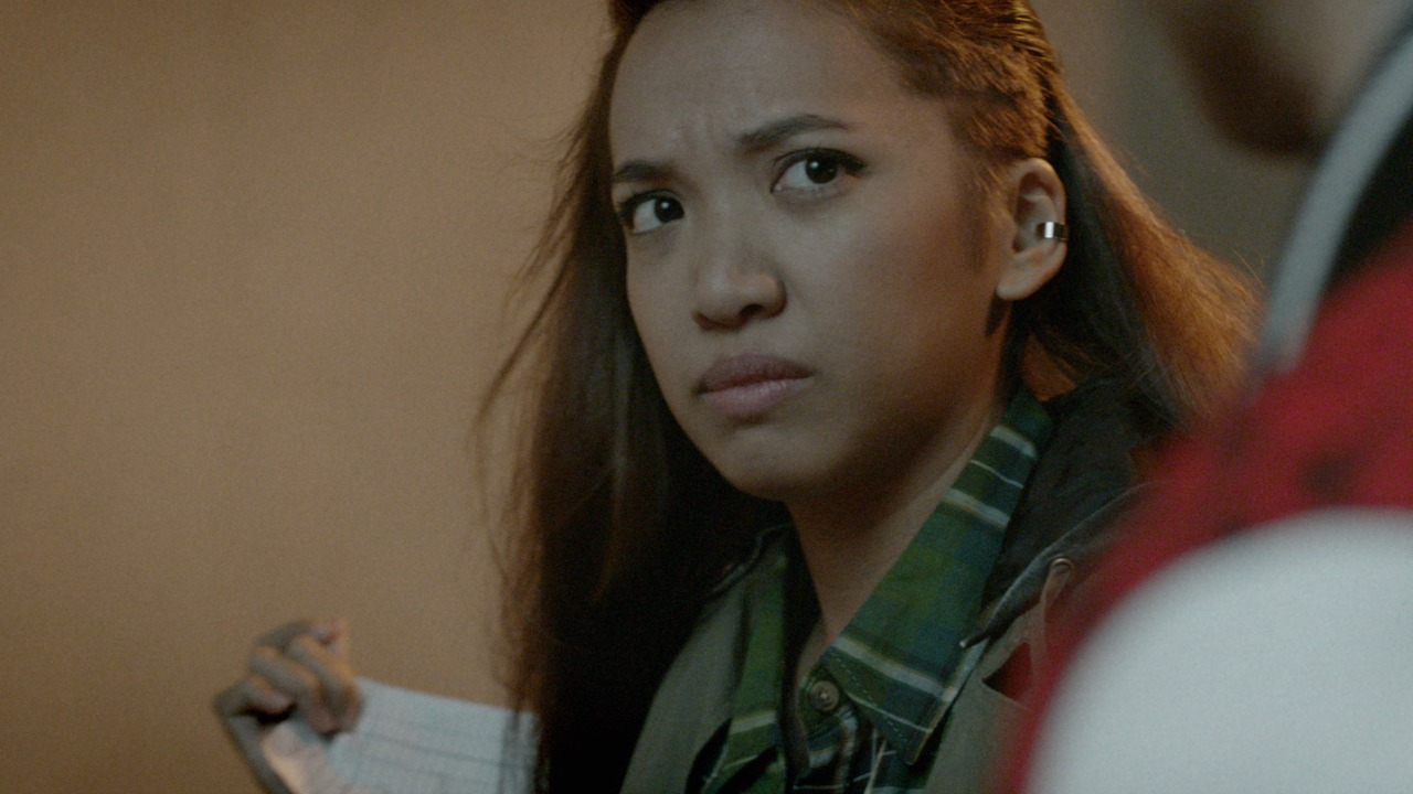 Jess dela Merced as Justine in 'Hypebeasts,' reading a racist fast food receipt.
