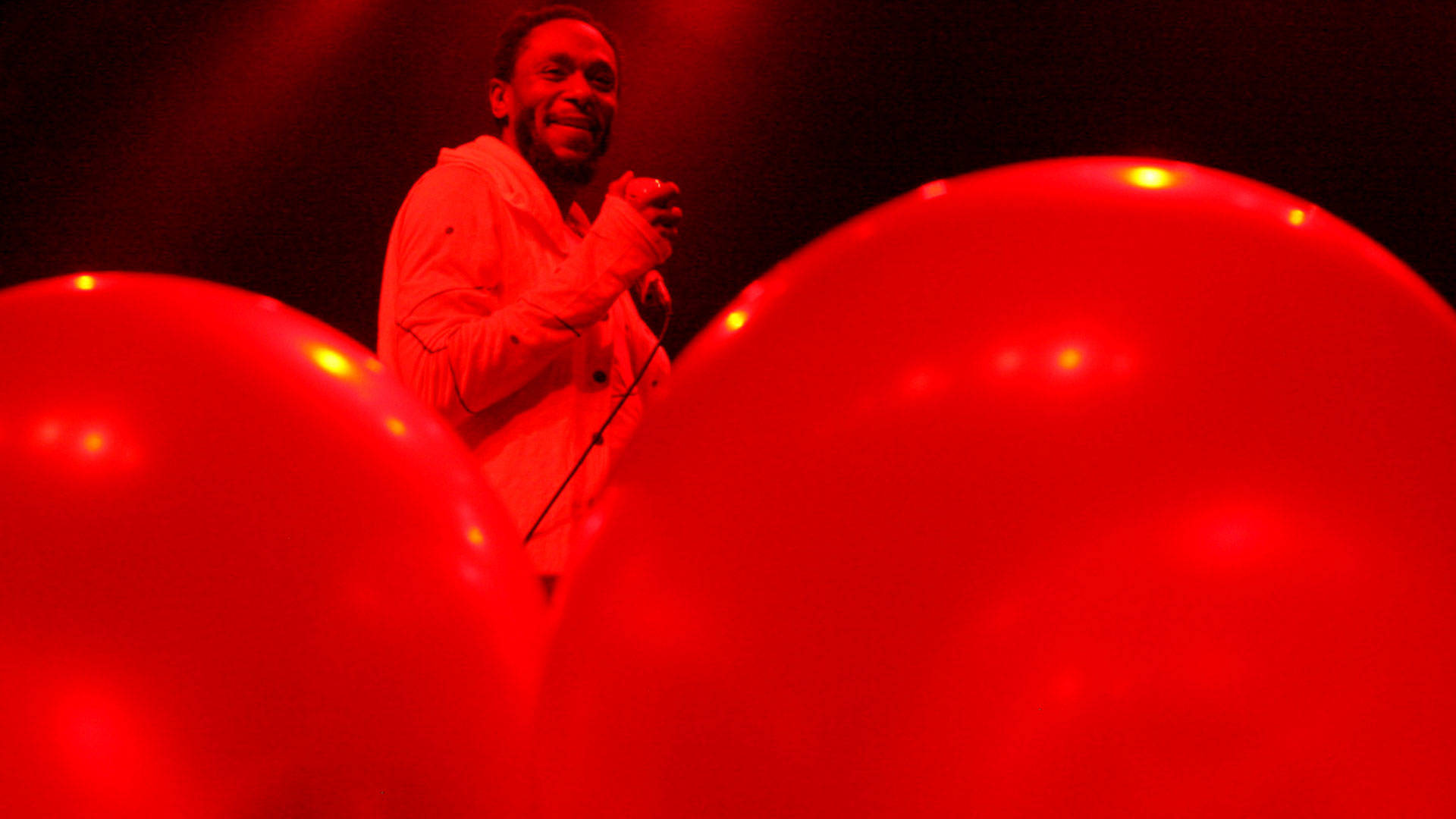 Mos Def, bathed in red light, performs at the Fox Theater in Oakland on Friday, Dec. 9, 2016. Photo: Gabe Meline/KQED