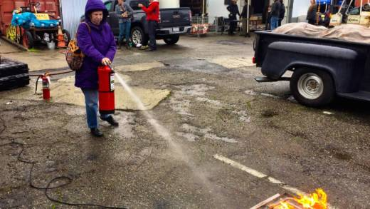 Artist Rose Kelly practices with a fire extinguisher at a training sponsored by We the Artists of the Bay Area