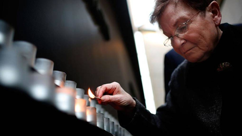 Holocaust survivor Josiane Traum lights a memorial candle during an International Holocaust Remembrance Day Commemoration at the United States Holocaust Memorial Museum on January 27, 2017 in Washington, DC.