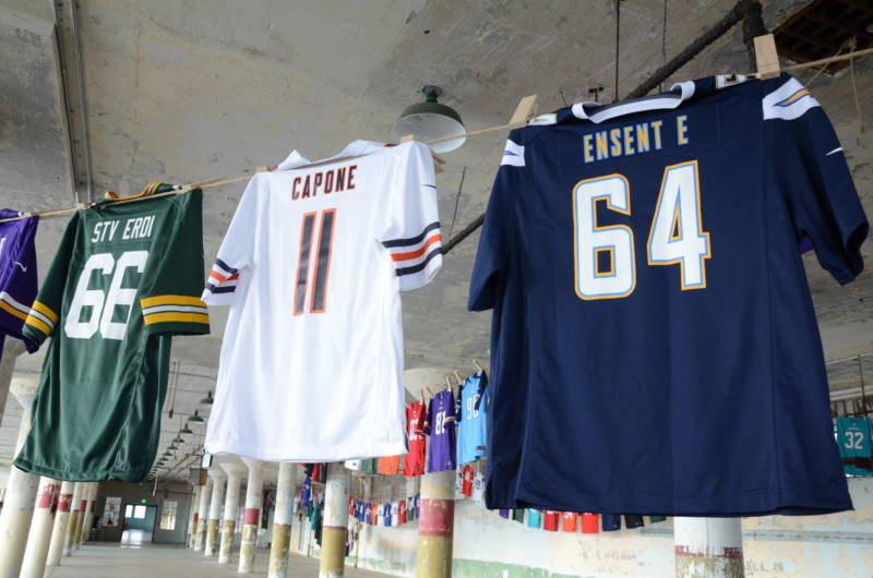 "A white number 11 Chicago Bears jersey with the name ""Capone"" is strung up as part of the art installation ""Shortening: Making the Irrational Rational"" at Alcatraz on Tuesday, October 25, 2016. According to the artist, the smaller Capone jersey signifies that Capone's sentence, 11 years, should have been longer unlike the nonviolent drug sentences he would like to see shortened."