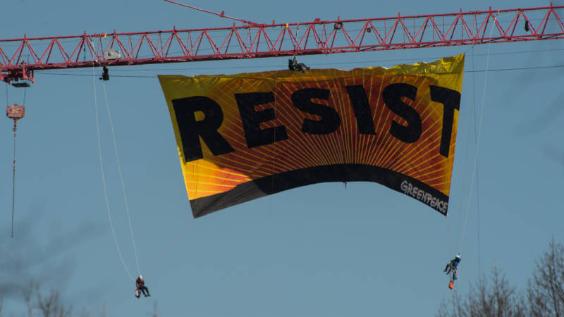"Greenpeace protesters unfold a banner reading ""Resist"" from atop a construction crane behind the White House January 25, 2017 in Washington, DC. The banner, flying high enough to be seen from the White House, is in opposition to the policies of President Donald Trump."