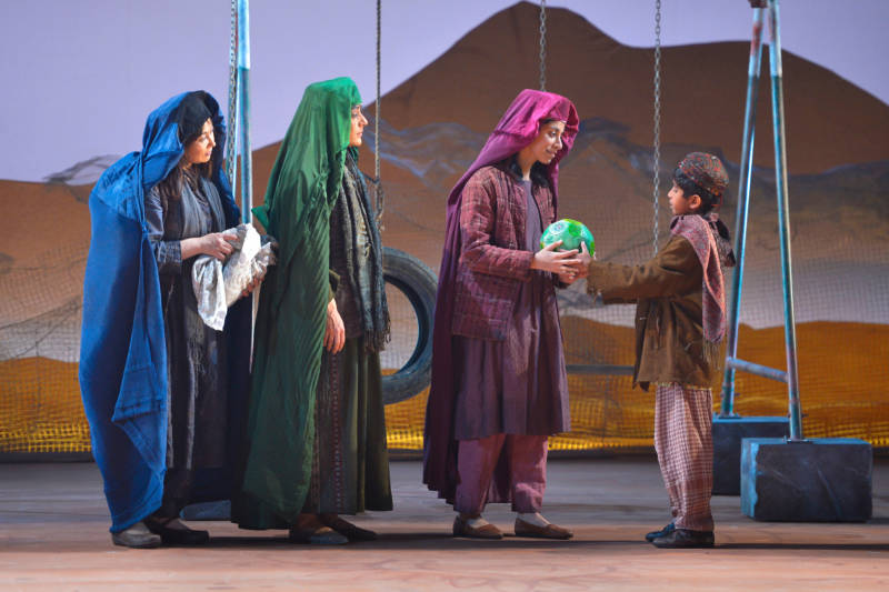 Mariam (Kate Rigg, left) and Laila (Nadine Malouf, center) look on as Zalmai (Neel Noronha), Laila's son, gives his sister Aziza (Nikita Tewani) a soccer ball in the world-premiere adaptation of Khaled Hosseini's novel, 'A Thousand Splendid Suns.'